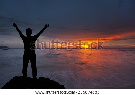 Silhouette of boy with hands raised to beautiful sunset  - stock photo