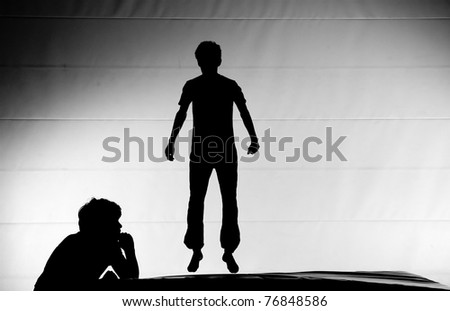 silhouette of boys on trampoline - stock photo