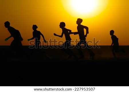 Silhouette of boys running in a field against a warm sunrise sky.  - stock photo