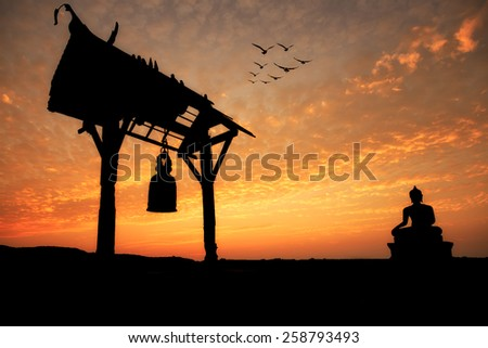 Silhouette of Buddha statue and bell at sunset in Saraburi, Thailand  - stock photo