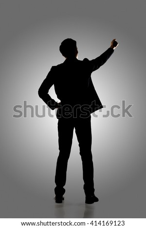 Silhouette of business man standing and writing, full length portrait isolated. - stock photo