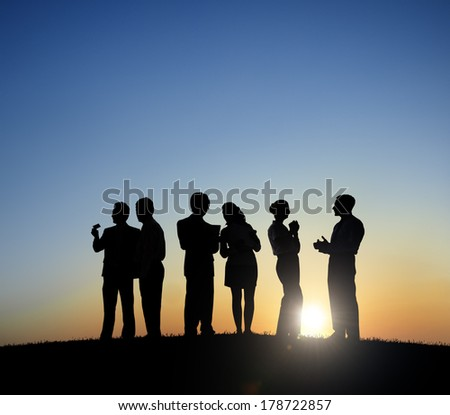 Silhouette of Business People Working at Sunset - stock photo