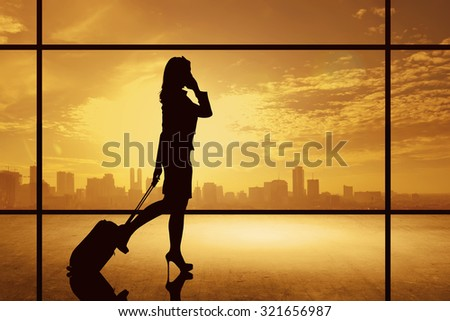 Silhouette of business woman walking with suitcase over city background. Business travel concept - stock photo
