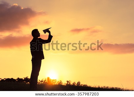 Silhouette of businessman throwing paper airplane.  - stock photo