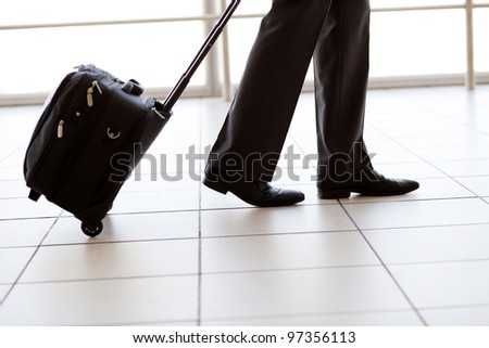 silhouette of businessman walking in airport - stock photo