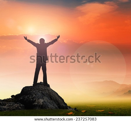 Silhouette of businessman with hands raised to beautiful sunset background. - stock photo