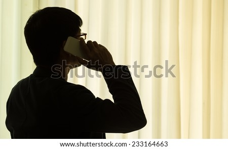 Silhouette of businessman with mobile phone - stock photo