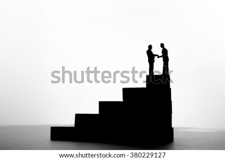 Silhouette of businessmen shaking hand on of wood stair. - stock photo