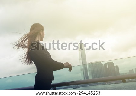 Silhouette of businesswoman stand and look far away in Hong Kong, Asia. - stock photo