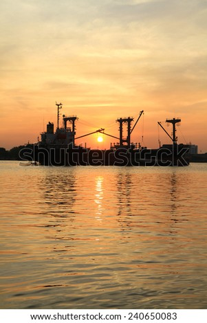 Silhouette of cargo ship in the river on twilight time - stock photo