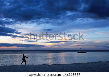 silhouette of child jumping in sunset on the beach - stock photo