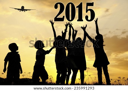 Silhouette of children running and jumping on the summer sunset meadow for happy new 2015 year - stock photo