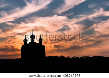 Silhouette of Christian church against colorful sunset sky  - stock photo