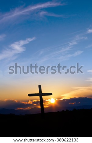 Silhouette of Christian cross at sunrise or sunset with light rays - stock photo