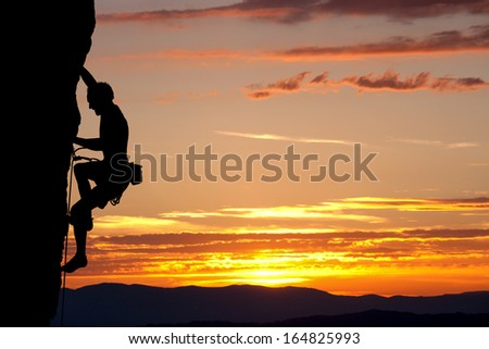 silhouette of climber on rock face  - stock photo