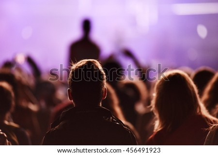 Silhouette of concert crowd in front of bright stage lights - stock photo