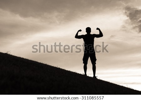 Silhouette of confident fit male outdoors.   - stock photo