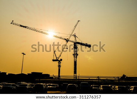Silhouette of construction site at sunset - stock photo