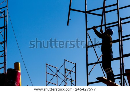 silhouette of construction worker against sky on scaffolding with ladder on building site - stock photo