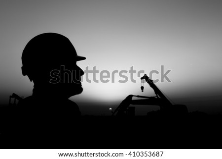 Silhouette of construction worker at construction site in oilfield - Blur background with heavy lifting equipment - Sunset - Black and white - stock photo
