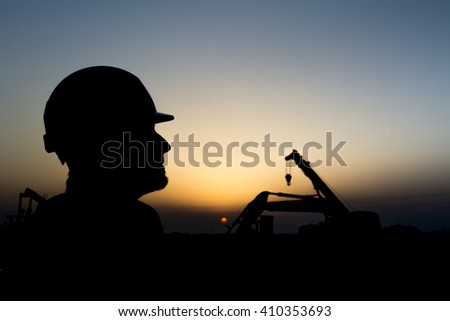 Silhouette of construction worker at construction site in oilfield - Blur background with heavy lifting equipment - Sunset.   - stock photo