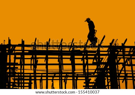 Silhouette of construction workers on scaffold working on a construction site  - stock photo