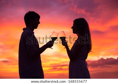 Silhouette of couple drinking wine at sunset  - stock photo