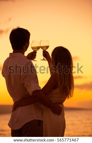 Silhouette of couple enjoying glass of champagne on tropical beach at sunset - stock photo