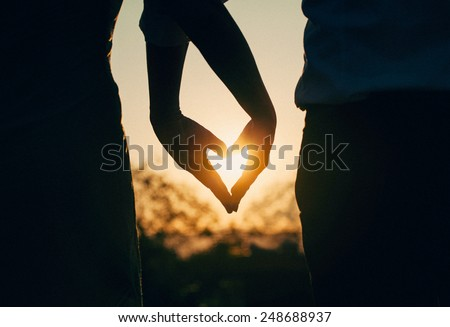 Silhouette of couple holding hands in heart shape with sunset in  the middle. Vintage, retro toned photo.  - stock photo