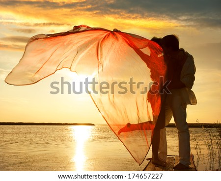 Silhouette of couple in love on sunset background - stock photo