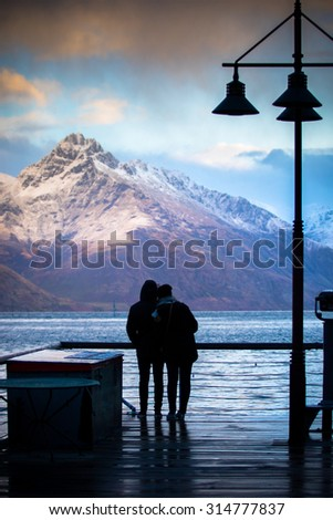 silhouette of couples love standing in wakatipu lake view point in queen town south island new zealand at beautiful scenic - stock photo