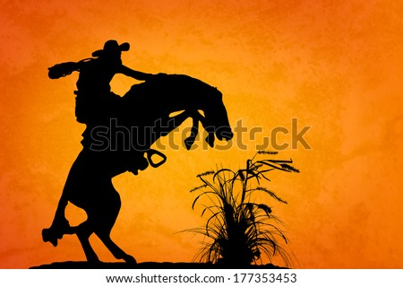 Silhouette of cowboy reigning bucking bronco spooked by something in the nearby sagebrush. Sunset orange/yellow textured background. - stock photo