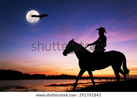 silhouette of Cowboy sitting on his horse at river full moon after sunset background - stock photo