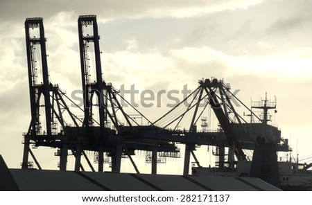 Silhouette of cranes on skyline in port shipping area, Auckland, New Zealand - stock photo