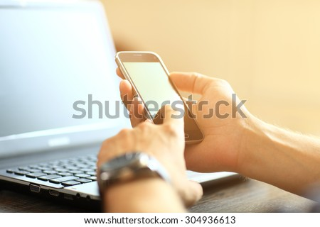 Silhouette of cropped shot of a young man working from home using smart phone and notebook computer, man's hands using smart phone in interior, man at his workplace using technology, flare light - stock photo