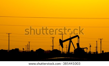 Silhouette of crude oil pump at  sunset in oil field. - stock photo