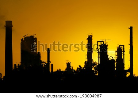 silhouette  of crude oil refinery station during sunset - stock photo