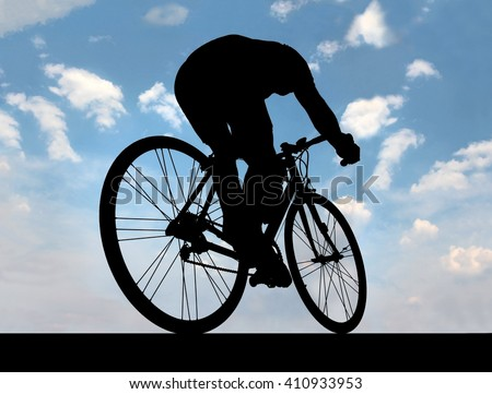 silhouette of cyclist against the blue sky when he goes on road, Black outline of a cyclist on a bike on a background of blue sky. - stock photo