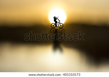 silhouette of cyclist with rucksack on beautiful sunset - stock photo