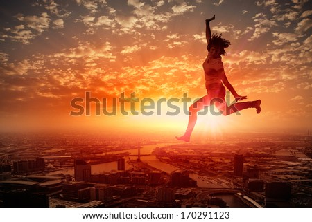 Silhouette of dancer jumping against city in lights of sunrise - stock photo
