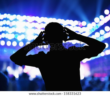 Silhouette of DJ wearing headphones and performing at night club - stock photo