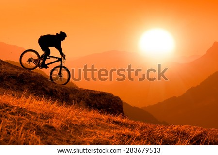 silhouette of downhill mountain bike rider at orange sunset - stock photo