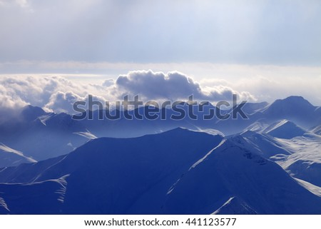 Silhouette of evening mountains in mist. Caucasus Mountains, Georgia, view from ski resort Gudauri. - stock photo
