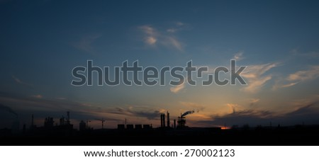 Silhouette of factory pipes polluting air - stock photo