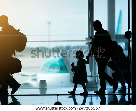 Silhouette of family at airport - stock photo