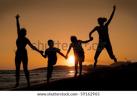 Silhouette of family jumping on the beach   on beautiful summer sunset - stock photo