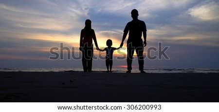 Silhouette of family on the beach at twilight. Concept of friendly family. (Shallow DOF, slight motion blur) - stock photo