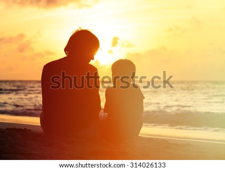 silhouette of father and little son looking at sunset on beach - stock photo
