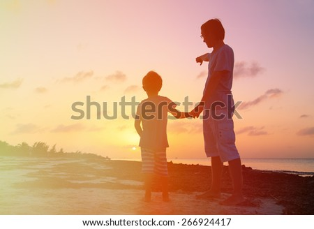 silhouette of father and son at sunset beach, father pointing at the sun - stock photo