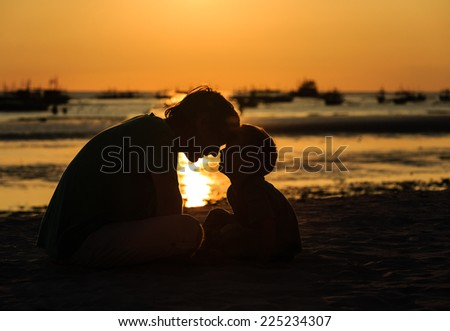 silhouette of father and son having fun on sunset beach - stock photo